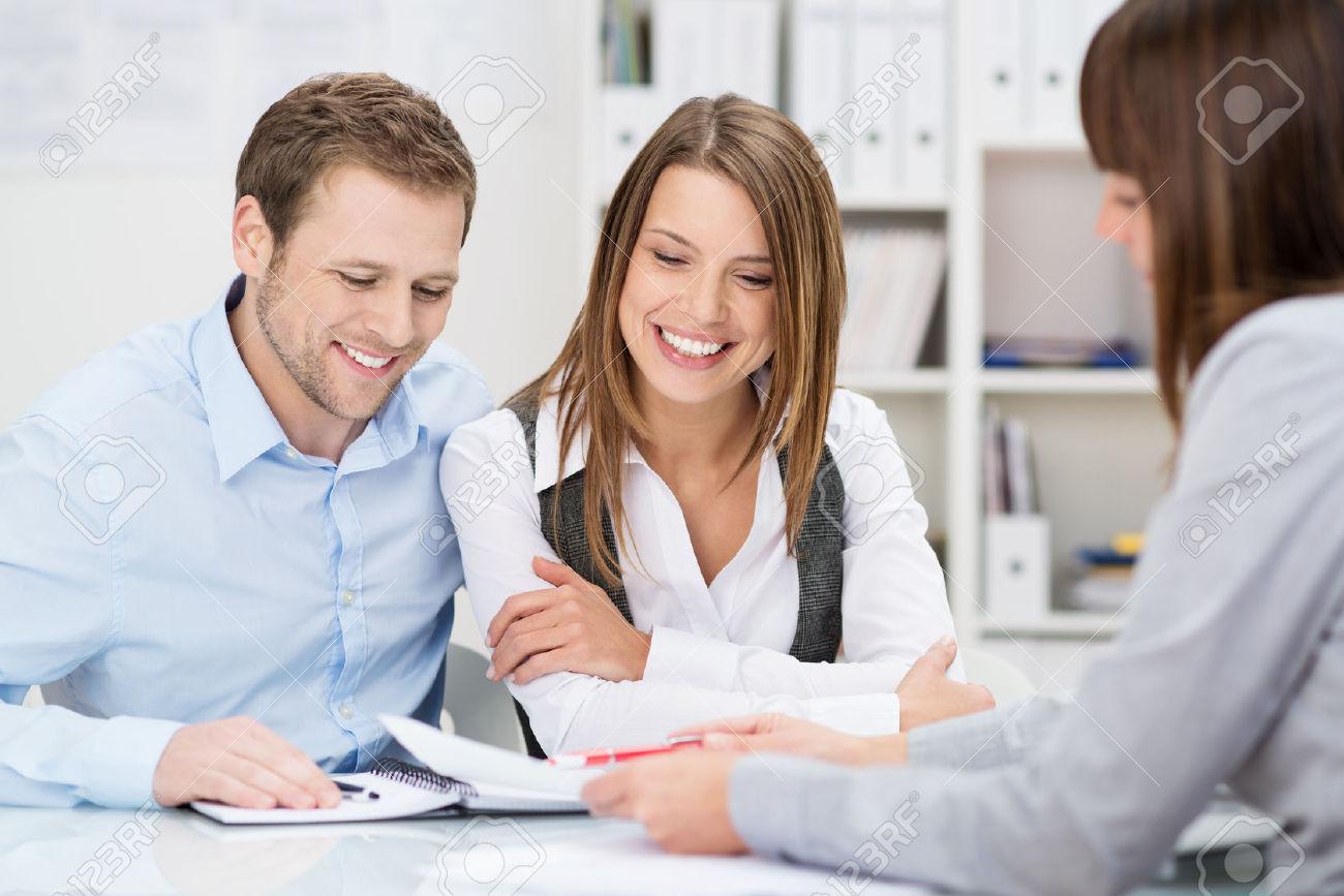 26572235-Consulente-per-gli-investimenti-che-una-presentazione-di-un-amichevole-giovane-coppia-sorridente-sed-Archivio-Fotografico